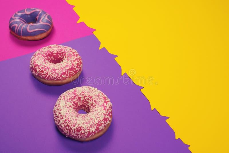 在多色的背景的三个五颜六色的油炸圈饼 库存照片