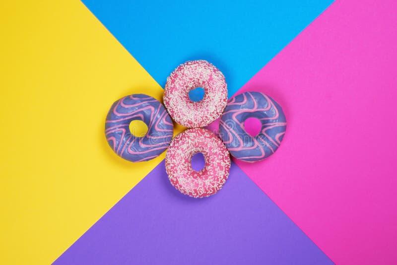 在多色的背景的四个油炸圈饼 图库摄影