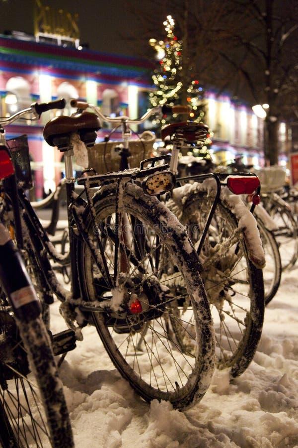 在多雪的圣诞节街道上的自行车 免版税库存照片