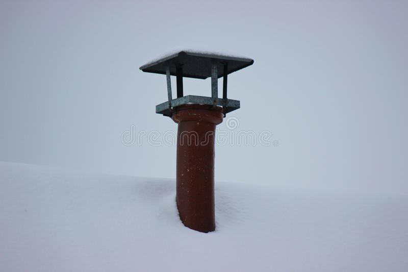 在多雪的屋顶的一个烟囱 多雪的冬天在村庄,暖气在有木头的老房子里 库存照片