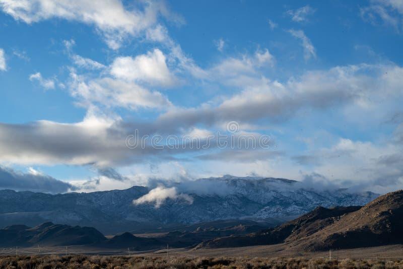 在多雪的山和小山,沙漠东部山脉Nevadas,加利福尼亚,美国的多云11月天空 免版税库存照片