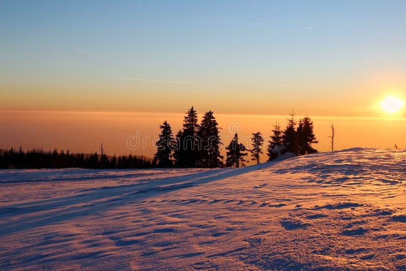 在多雪的山和烟雾的日落在谷 库存图片