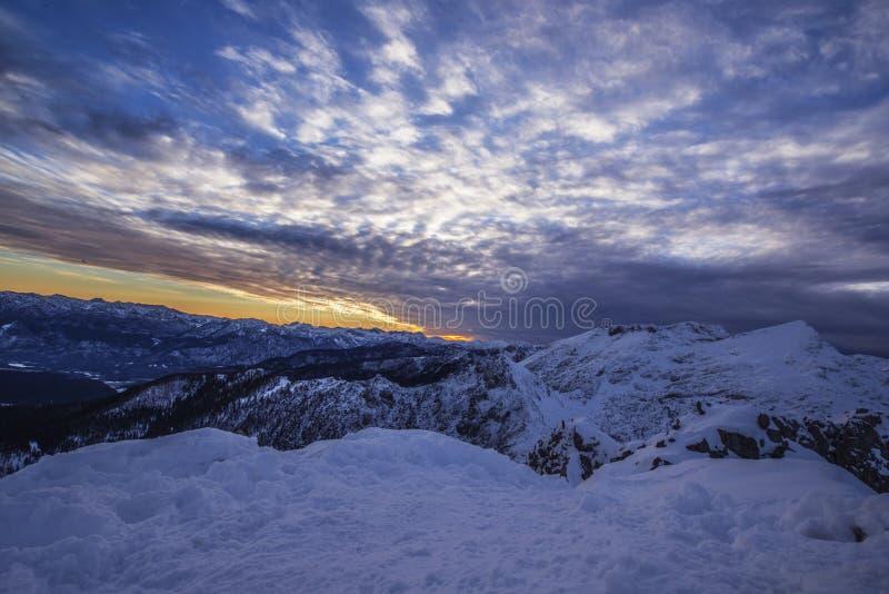 在多雪的山的日落在壮观的大气 库存图片