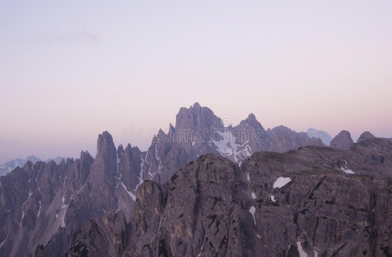 在多雪的山的日落在壮观的大气 图库摄影