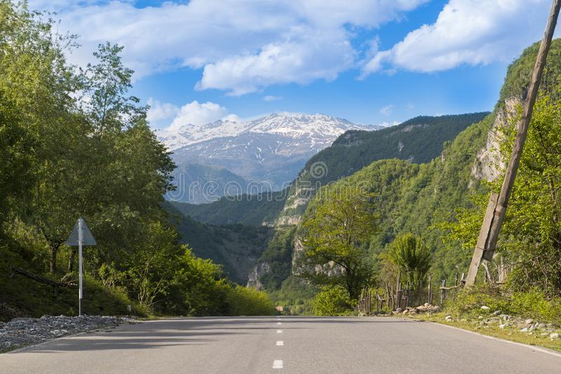 在多雪的山背景的好路  免版税库存照片