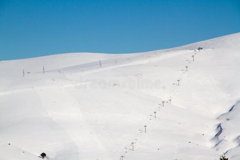 在多雪的山背景的滑雪轨道  免版税库存照片
