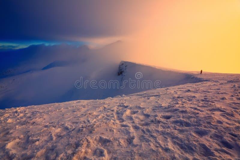 在多雪的岩石的边缘某人站立 在雾,早晨天空的高山 免版税库存图片