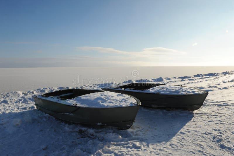 在多雪的海岸冬天沿海风景的两条被放弃的小船在一好日子 冻结河 清楚的天空 露天场所 免版税库存照片