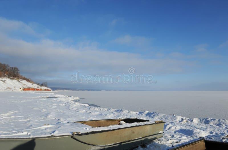 在多雪的海岸冬天沿海风景的两条被放弃的小船在一好日子 冻结河 清楚的天空 露天场所 库存图片