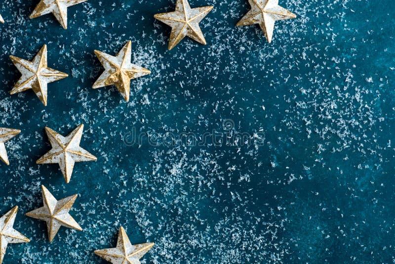在多雪的深蓝背景的白色金黄星 圣诞节新年贺卡海报横幅 减速火箭的样式葡萄酒 免版税库存照片