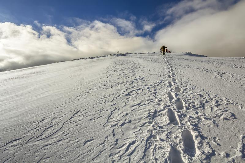 在多雪的走与在山的背包的小山与脚印和很远远足者的宽看法 库存照片