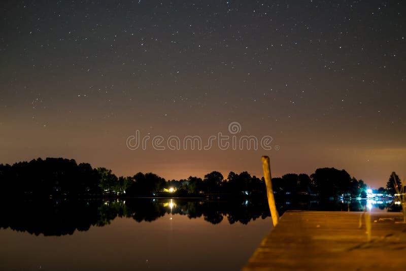 在夜、星天空和湖里环境美化 免版税库存图片