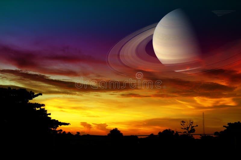 在夜云彩日落天空的土星后面,在地球附近的概念土星 库存照片