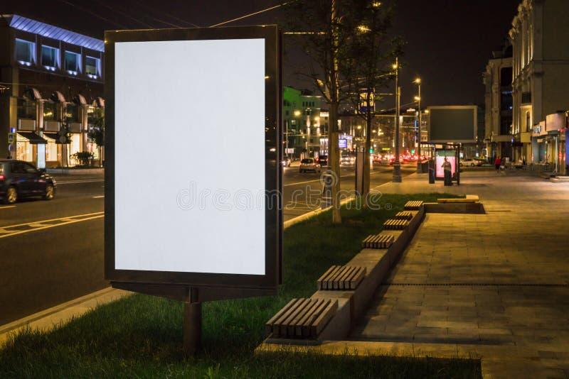 在夜城市街道上的垂直的空白的发光的广告牌 在背景大厦和路有汽车的 嘲笑 免版税库存照片