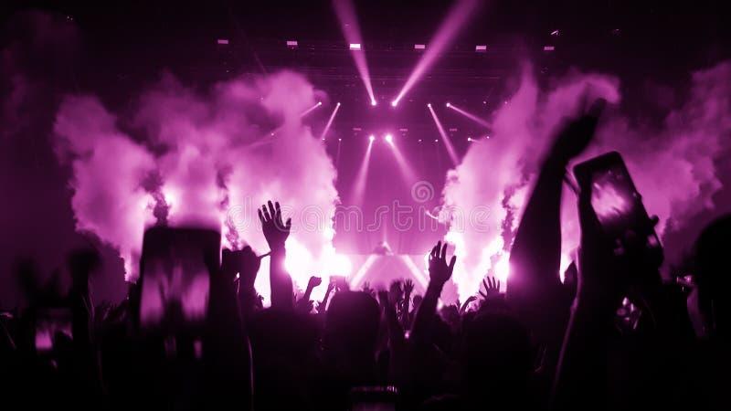 在夜总会党音乐会的愉快的人舞蹈 免版税库存照片