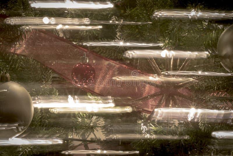在夜明亮和愉快的光的圣诞节装饰品与丝带和闪烁 免版税图库摄影