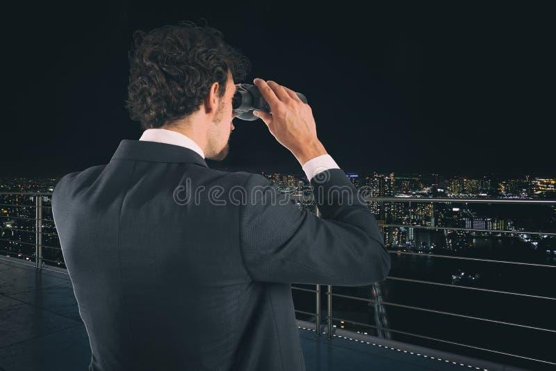 在夜期间,商人看有双筒望远镜的城市 未来和新的商机概念 免版税图库摄影
