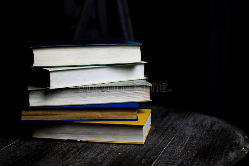 在夜期间,堆在圆材桌上的旧书与读光 免版税库存图片