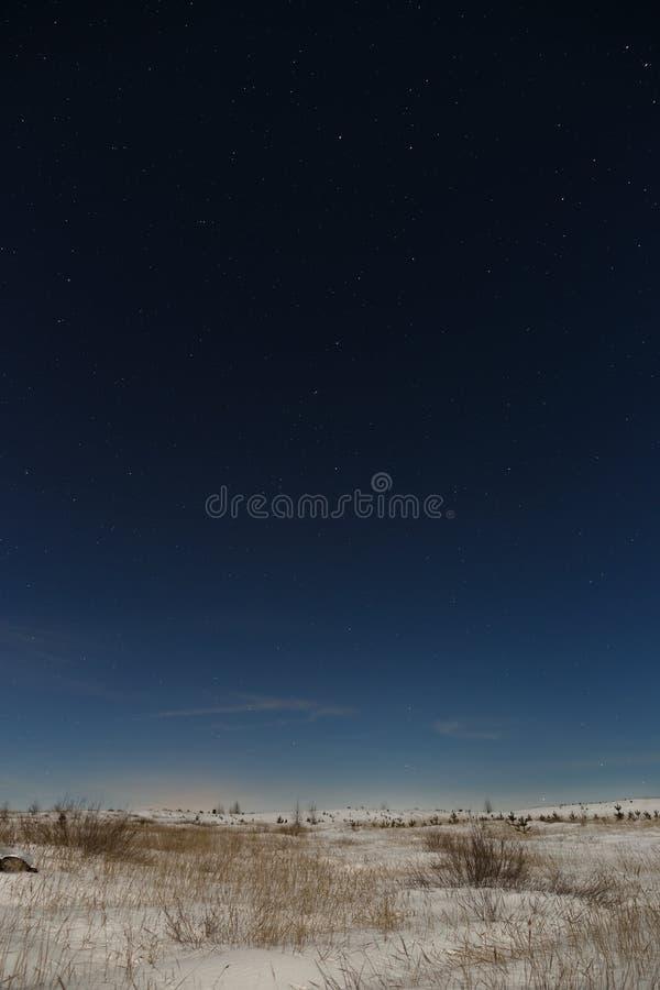 在夜空的星在积雪的平原 外层空间背景被拍摄在满月下 免版税库存照片
