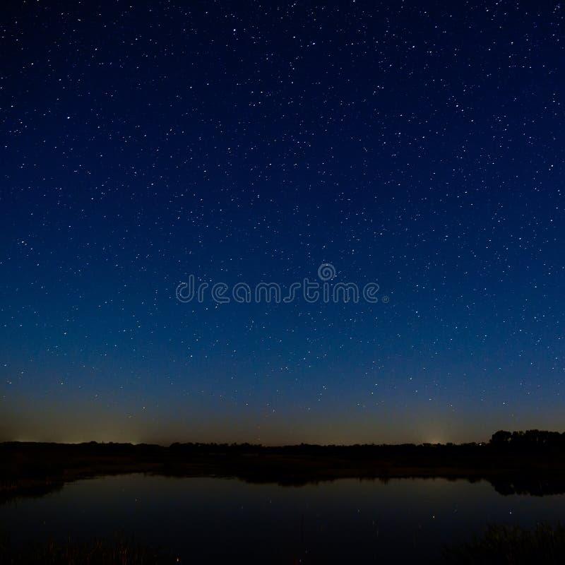 在夜空的星形 与一光滑的surfac的夜风景 免版税库存图片