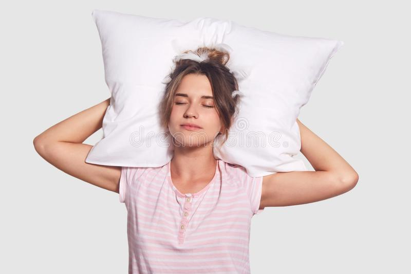 在夜间期间,宁静的可爱的年轻女性水平的射击有闭合的眼睛的,保留在头后的枕头,看宜人的梦想, 免版税库存照片