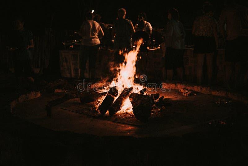 在夜间营火人的木燃烧在背景中 免版税库存照片