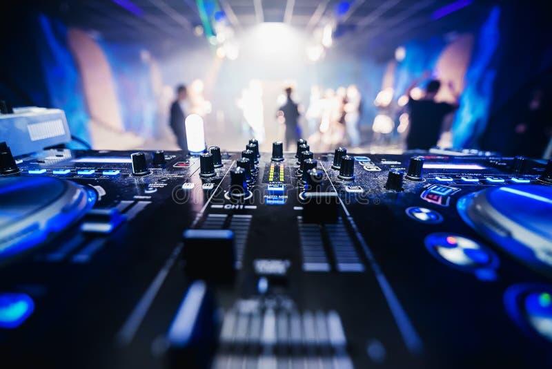 在夜总会特写镜头的音乐设备DJ与被弄脏的背景跳舞人民 免版税图库摄影