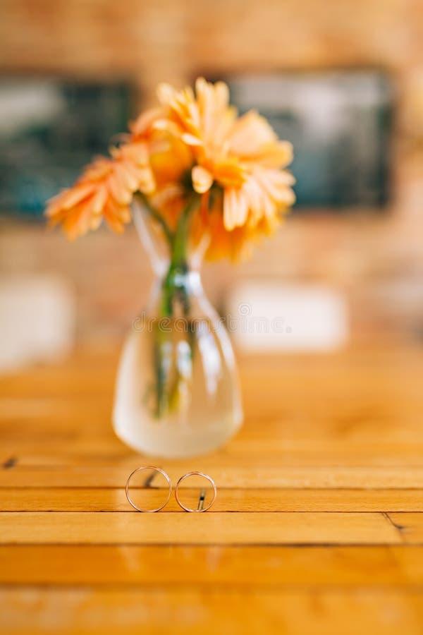在大丁草花瓶背景的婚戒  婚礼j 免版税库存照片