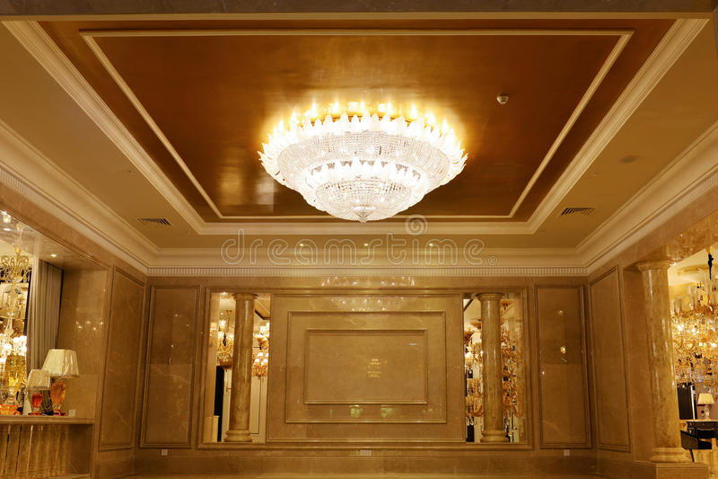在大厅里装饰的豪华水晶枝形吊灯照明设备 免版税库存照片