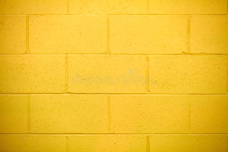 在大厦一边的明亮的黄色外部砖墙 免版税库存图片