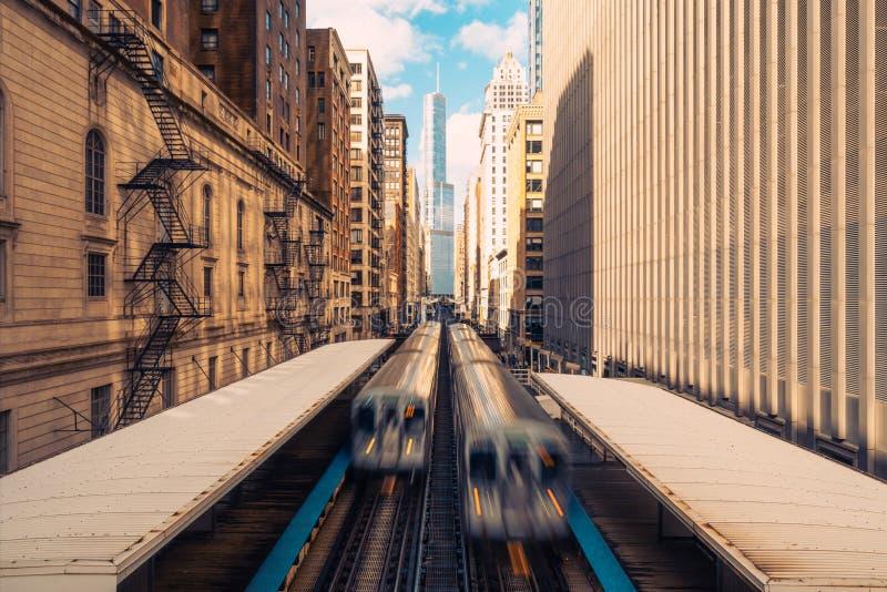 在大厦之间的火车到达的火车站在街市芝加哥,伊利诺伊 公交或者美国城市生活 免版税库存图片