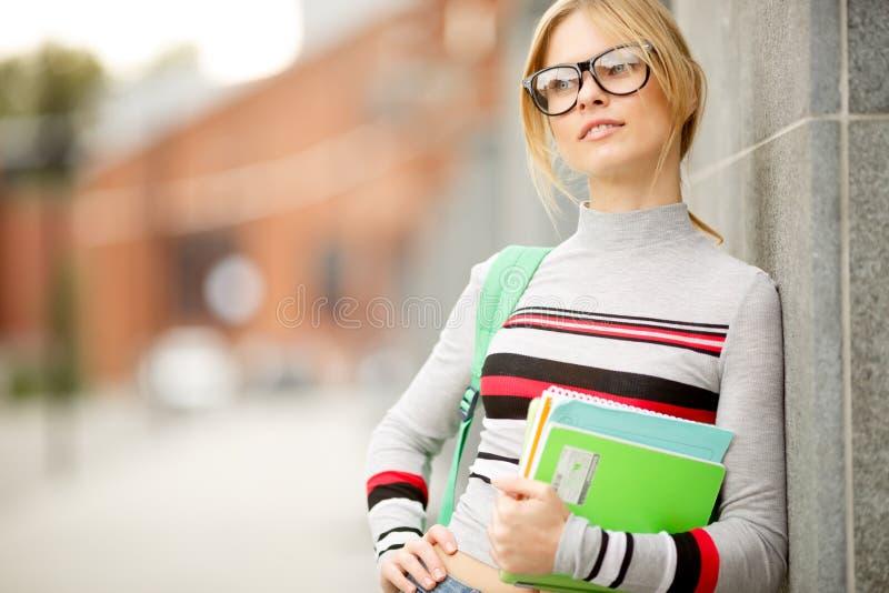 在大厦墙壁倾斜的白肤金发的女孩  免版税图库摄影