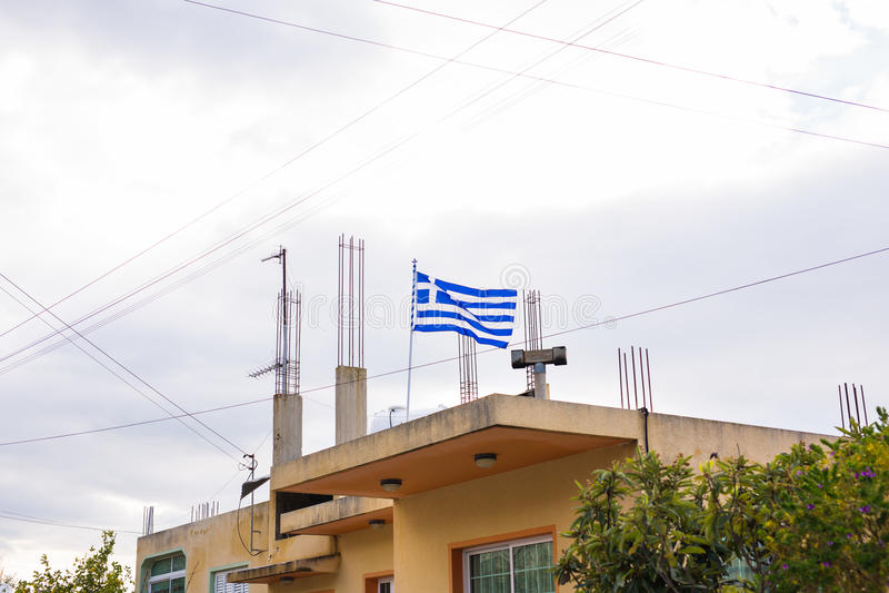 在大厦屋顶的希腊旗子,挥动在风 免版税图库摄影