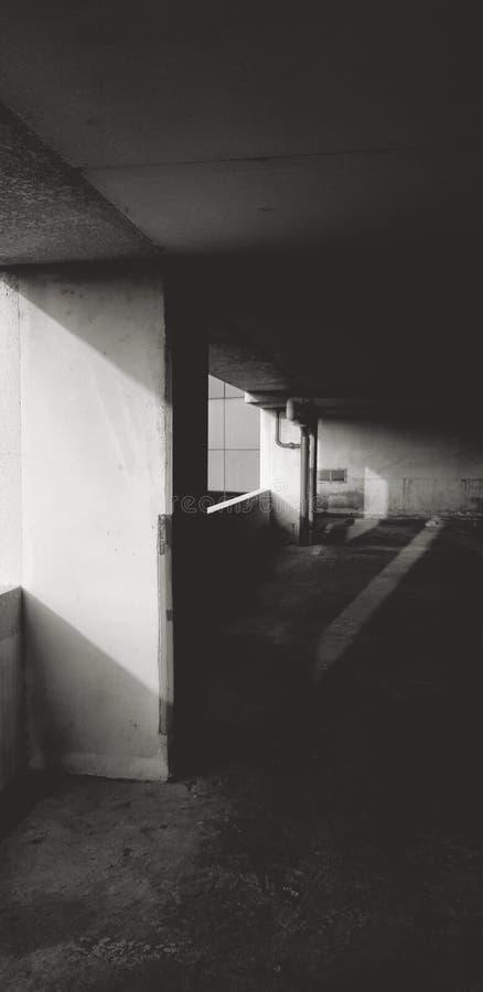 在大厦的停车处与从左边、水管道和黑暗的阳光 免版税图库摄影