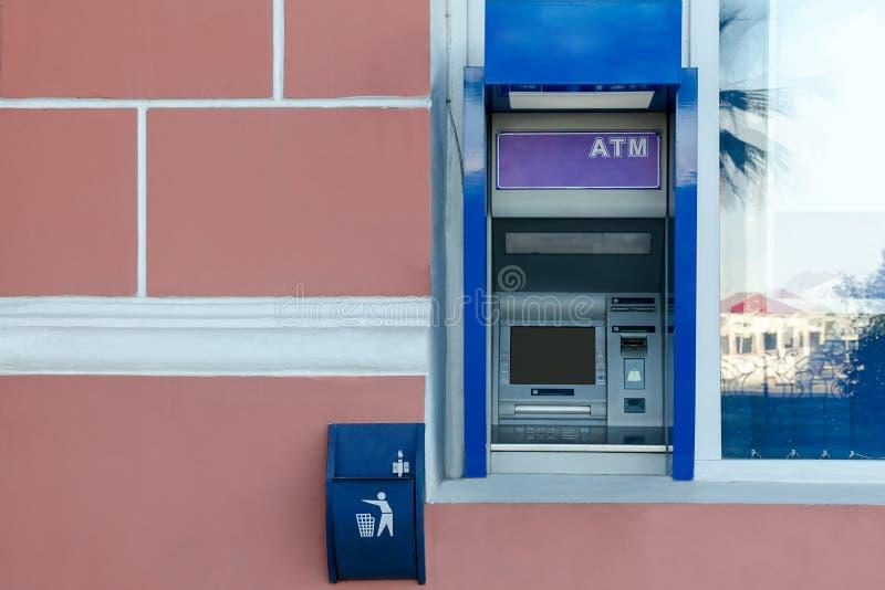 在大厦的墙壁的ATM在窗口附近的,在它附近一个小垃圾箱和检查 免版税库存图片
