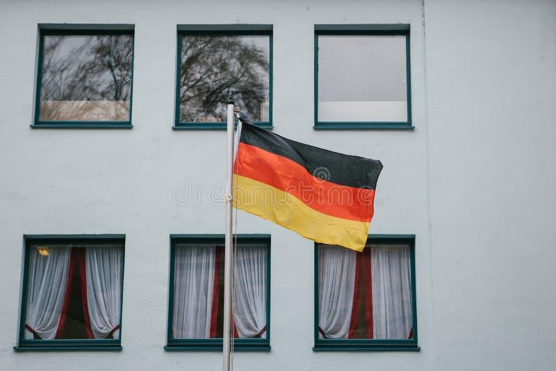 在大厦的外部的德国旗子在窗口旁边的 在竞选前的爱国情绪 库存图片