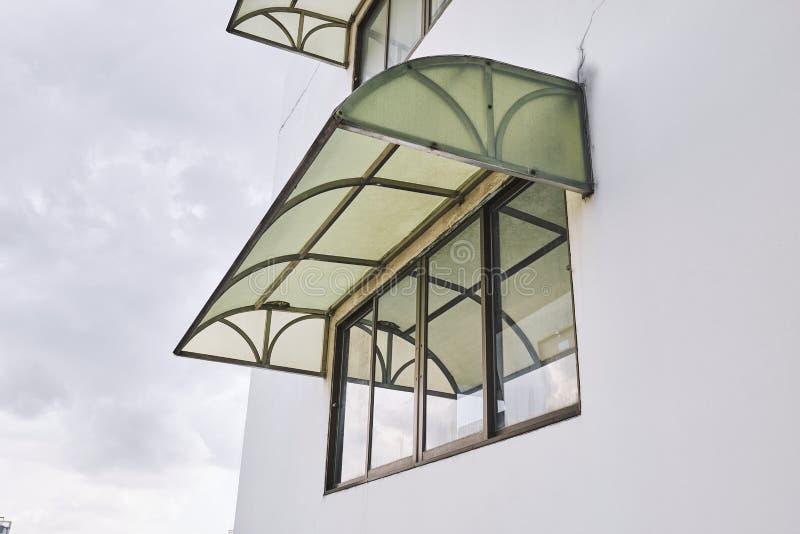 在大厦盖子之外登上的老绿色遮篷窗口 库存图片