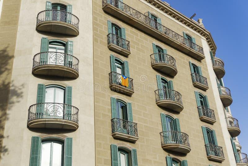 在大厦阳台的巴塞罗那,西班牙加泰罗尼亚的旗子 免版税库存照片