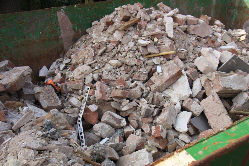 在大型垃圾桶的残破的砖 库存图片