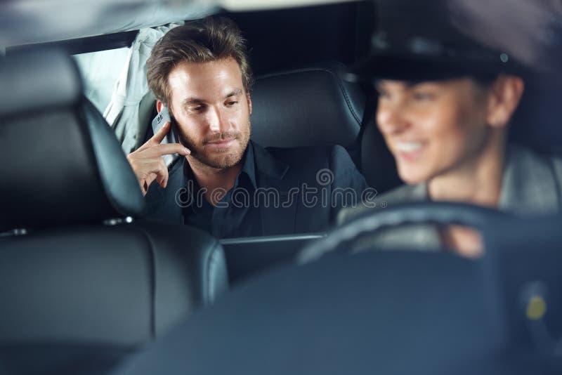 在大型高级轿车汽车夫驾驶的商人 库存照片