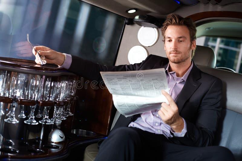 在大型高级轿车的英俊的人读书报纸 库存图片