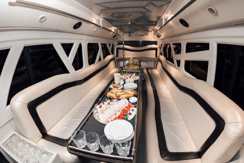 在大型高级轿车里面的内部 当沙发和桌用快餐盖为假日 选择聚焦 免版税库存图片