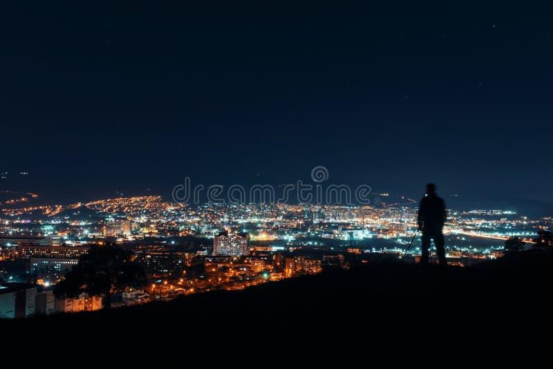 在大城市的夜 摄影师在小山顶部的剪影身分在城市,做夜摄影 库存图片