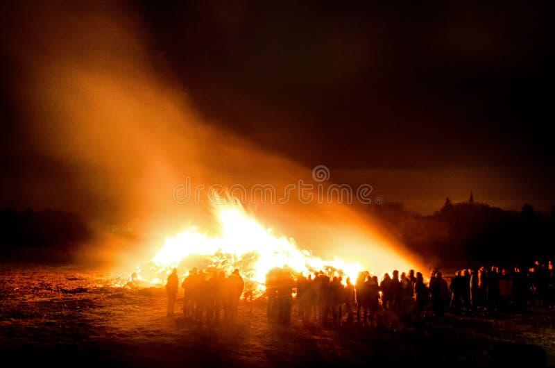 在大复活节篝火附近的村民 免版税库存照片