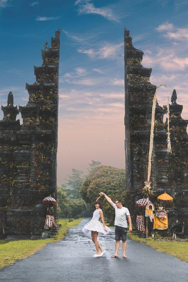 在大巴厘语门背景的年轻蜜月夫妇 可视巴厘岛美丽的印度尼西亚海岛kuta人连续形状日落的城镇 库存图片