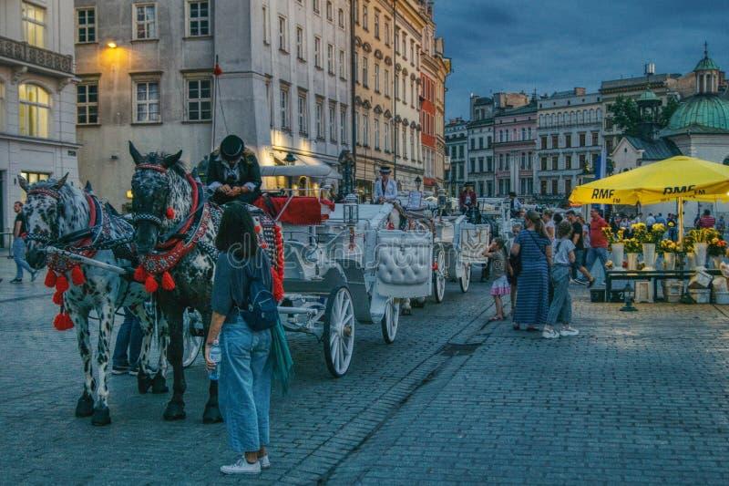 在大广场的克拉科夫,当夜接近并且点燃第一盏灯 免版税库存照片