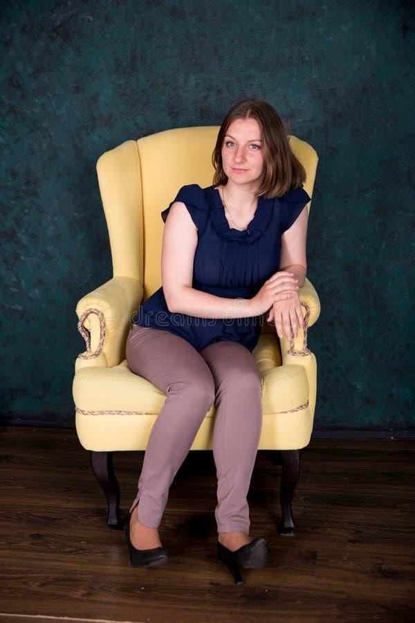 在大扶手椅子的美女开会在演播室 库存图片