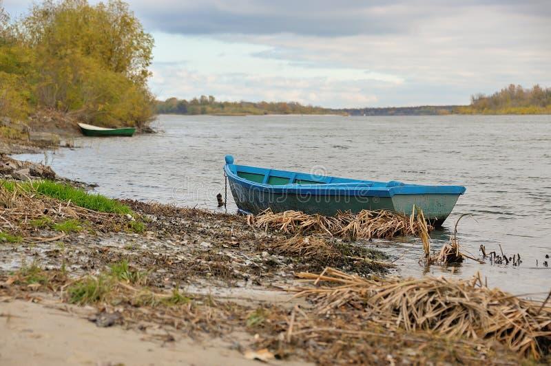 在大河的河岸的小船 免版税库存照片