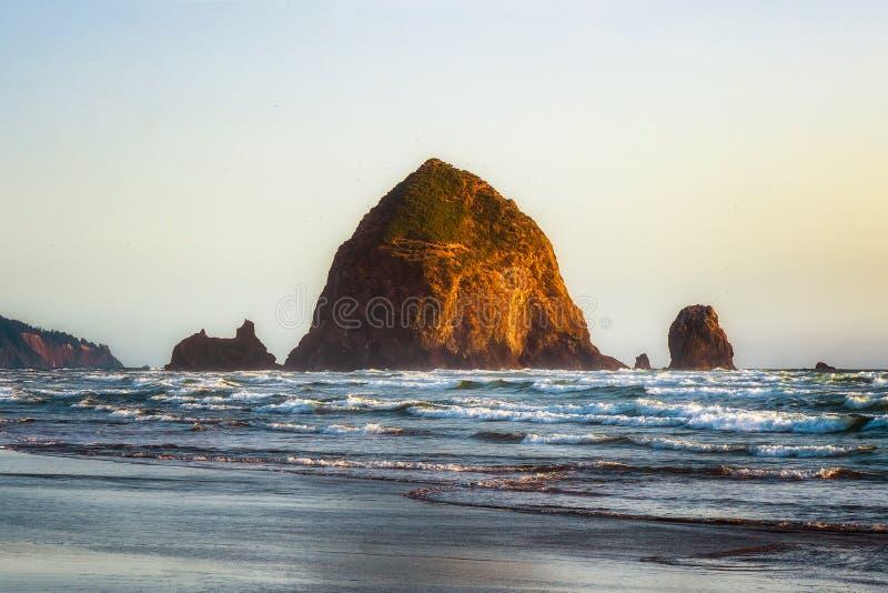 在大浪的干草堆岩石海堆在日落 位于大炮海滩的自然偶象地标,俄勒冈海岸 库存图片