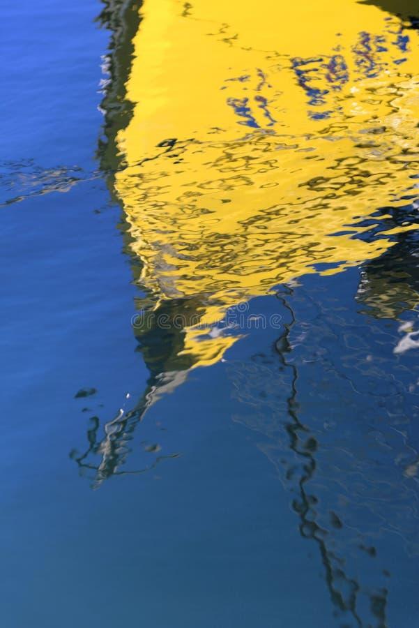 在大海的黄色小船反射 免版税库存照片